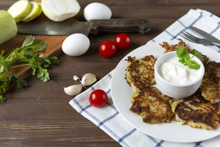 plate with zucchini pancakes with sour cream and herbs on a wooden background, knife, fork, fresh vegetables, cherry tomatoes, garlic, towel 版權商用圖片
