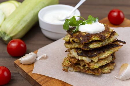 zucchini pancakes with sour cream and herbs on a Board, cherry tomatoes, garlic, , fresh raw zucchini