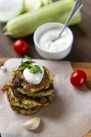 zucchini pancakes with sour cream and herbs on a Board, garlic, cherry tomatoes, fresh raw zucchini