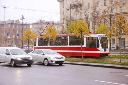 cars, tram on the road in St. Petersburg autumn cloudy day, October 2019, traffic, buildings in the city center, trees with yellow fallen leaves