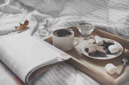 1 Cup of black coffee, saucer with cookies, marshmallows, chocolate pieces on a tray on a white plaid, open magazine, maple dry autumn leaves,