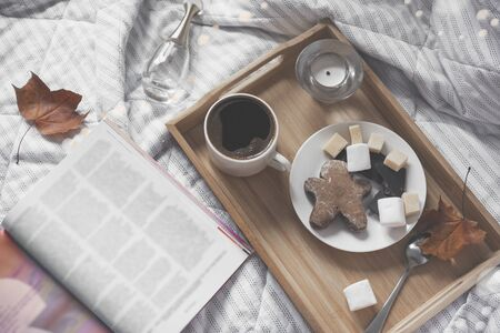 Cup of black coffee, a saucer with cookies, marshmallows, gingerbread man slices of cheese and chocolate on a tray on a white plaid, an open magazine, maple dry autumn leaves, a candle, a top view