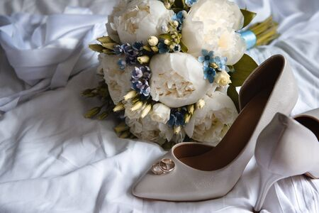 wedding bouquet of white peonies and blue flowers, white stiletto pumps with 2 gold wedding rings on a white sheet