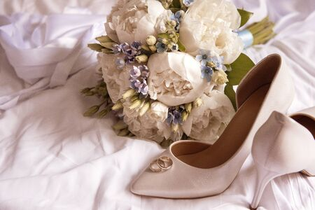 wedding bouquet of white peonies and blue flowers, white stiletto pumps with wedding rings on a white sheet