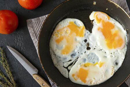 scrambled, fried eggs in a pan close-up, thyme, tomatoes, knife