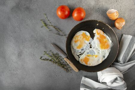 several fried eggs with tomato and thyme in a pan on a gray background, knife, towel, shell, top view, copy space