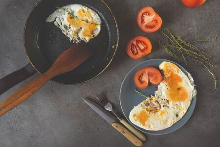 fried eggs with thyme and tomato on a plate, fried eggs in a pan, fork, knife on a gray background