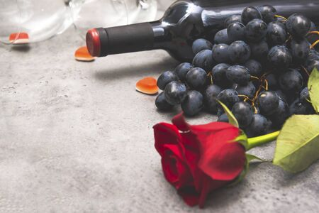 1 red rose, bottle of red wine, dark grapes, glass, hearts on a gray background, copy space, f