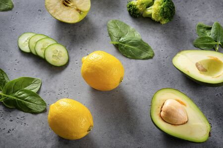 Apple, half avocado halves with a stone, broccoli, fresh green spinach leaves, yellow lemon, cucumber slices a blank sheet of Notepad on a gray background, top view, flat lay Фото со стока