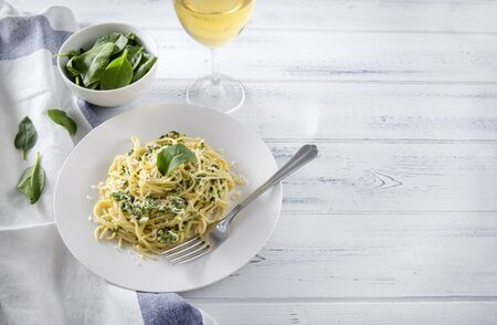 1 plate of pasta with spinach and cheese, a glass of white wine, a towel on a white wooden background Archivio Fotografico