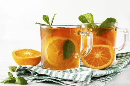 tea with orange, mint on a towel on a white background Banco de Imagens