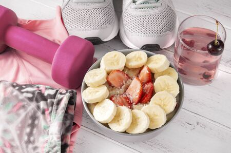 plate of oatmeal porridge with fresh strawberries and banana slices,  glass of cherry lemonade,  pink dumbbell, a sports top , gray sneakers on a white wooden background Zdjęcie Seryjne