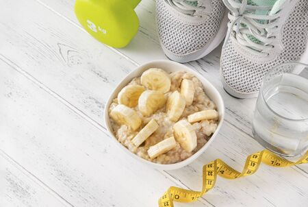 bowl of porridge with banana slices, a green dumbbell, measuring tape, glass of water ,gray sneakers on a white wooden background top view