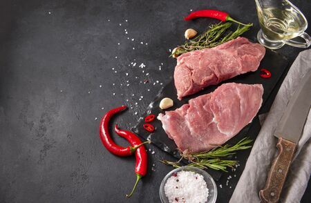 2 pieces raw meat with garlic, rosemary and red chili pepper, salt, oil on a black background, pork, knife, napkin