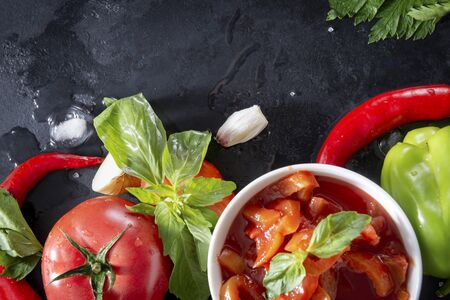 fresh Lecho with a sprig of green Basil, tomato slices, red chili pepper, garlic, ice cubes, on a black background, sauce top view,