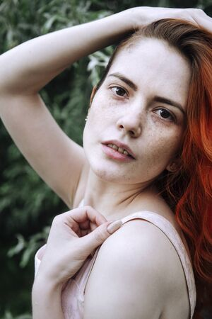 portrait of 1 young white woman with red hair and freckles, face of a European beautiful girl against a background of greenery 版權商用圖片