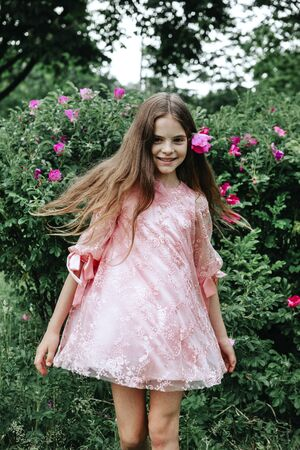 1 white girl 10 years old in a pink dress whirls against the background of greenery in the Park