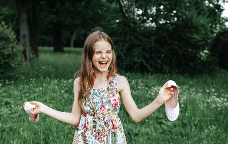1 white girl 10 years old in a dress holding shoes in her hands and laughing in a clearing in nature rejoicing in nature