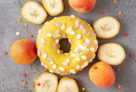 1 donut with yellow glaze, banana slices, fresh apricots on a gray background, baking,
