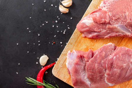 2 pieces of raw meat on a kitchen Board with garlic and red chili pepper on a black background, pork, Reklamní fotografie