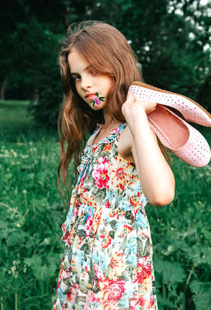 girl with long hair in a dress a dress with shoes in her hands on a background of greenery, teenager Stock fotó