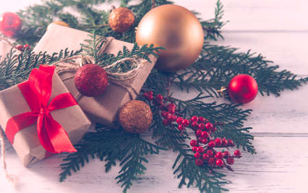 boxes with gifts on spruce branches, Golden and red Christmas balls, white and red bows on a white wooden background, Christmas still life, 免版税图像