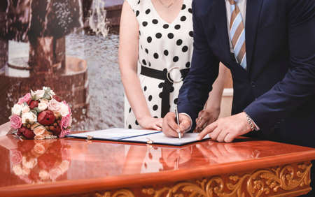 man and woman get married, sign marriage documents, groom, bride, bouquet, wedding