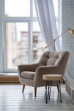1 beige chair in a bright room with a window background