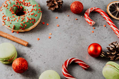 lollipops, cone, cinnamon stick, green donut, cookies, macaroon, red Christmas balls on a gray background, Christmas sweets