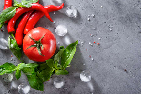 several red chili peppers, green Basil sprigs, 1 red tomato, spices, salt, ice cubes on a gray background top view
