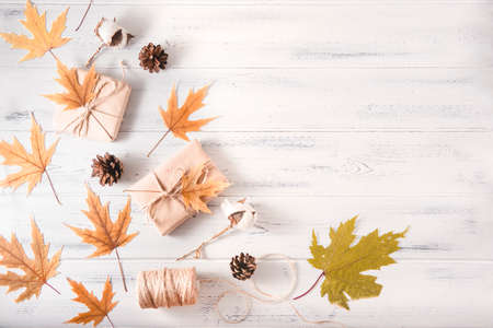 autumn yellow maple leaves, cones, thread on a white wooden background 免版税图像