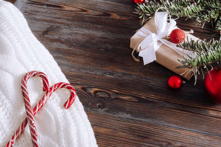 lollipops on a white sweater, spruce branch, red Christmas balls, gift on a wooden background