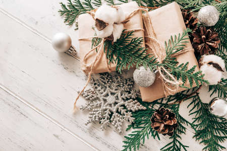 boxes with gifts on spruce branches, silver Christmas balls, a sprig of cotton, cones, snowflake on a white wooden background, Christmas still life, 免版税图像