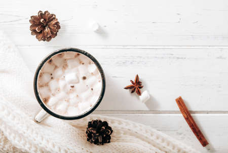 hot chocolate, cocoa mug with marshmallows, white sweater, cones, cinnamon sticks, star anise on a white wooden background, hot winter drink, place for inscription
