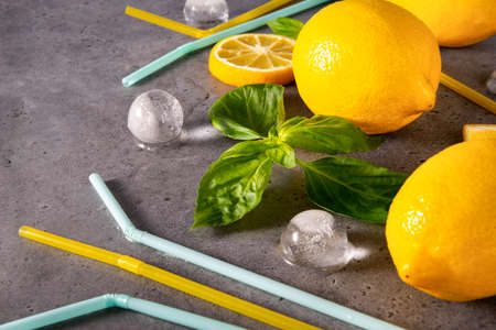 yellow whole lemons and slices, green Basil, ice cubes, yellow tubes on a gray background close up
