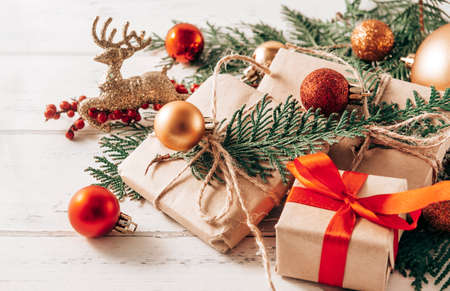 boxes with gifts on spruce branches, Golden and red Christmas balls, cones, toy deer, white and red bows on a white wooden background, Christmas still life, 免版税图像