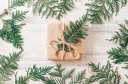 1 box with a gift for green branches of thuja, fir branches on a white wooden background, coniferous branches