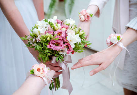 bride with a bouquet, bridesmaids' hands with flowers, wedding, hen party Stockfoto