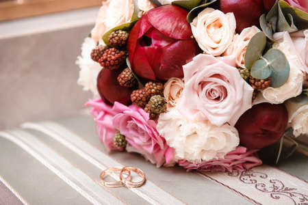 bride bouquet of maroon and pink peonies, white roses, 2 gold wedding rings, wedding decor, flowers