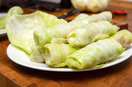 raw cabbage rolls with meat and rice, stuffed cabbage on a white plate