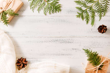 gift box, green thuja branches, fir branches, cones, white knitted sweater on a white wooden background, coniferous branches 免版税图像