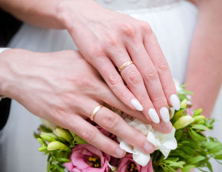 hands of the bride and groom with gold wedding rings on the background of a bouquet, newlyweds, wedding