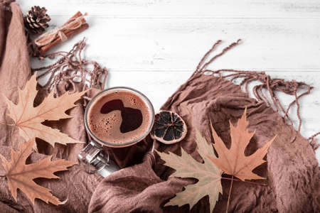 Cup of black hot coffee, autumn yellow maple leaves next to a brown scarf, a blanket on a white wooden background