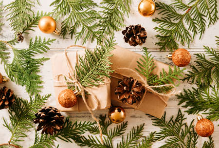 2 boxes with gifts for green branches of thuja, cones, Golden Christmas balls on a white wooden background, coniferous branches 免版税图像