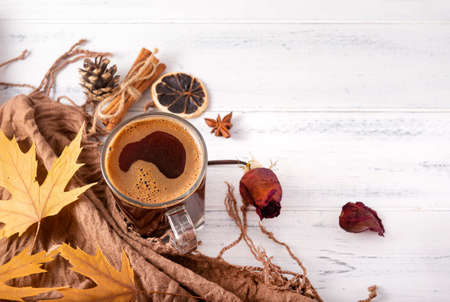 Cup of black hot coffee, autumn yellow maple leaves, cones, cinnamon sticks, dried rose next to a brown scarf, a blanket on a white wooden background