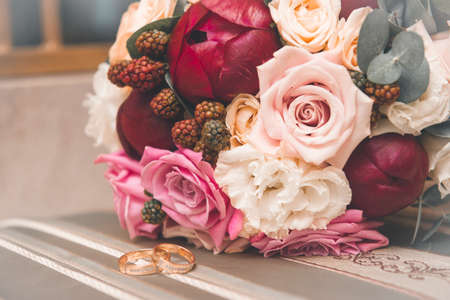 bride bouquet of red and pink peonies, white roses, 2 gold wedding rings, wedding decor, flowers 免版税图像