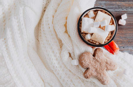 1 red cocoa mug with marshmallows, cookies on a white sweater on a brown wooden background