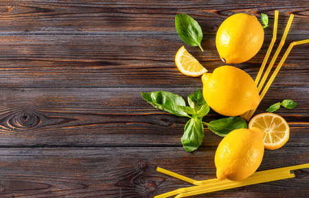 3 yellow whole lemons and slices, sprigs of green Basil, yellow tubes on a dark wooden background