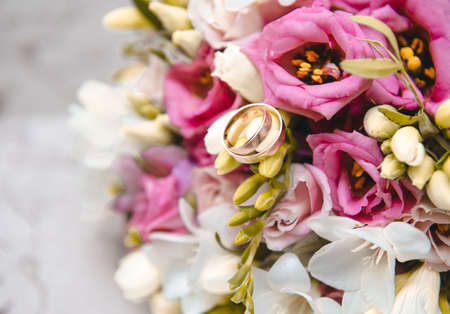 Bridal bouquet with pink and white flowers, 2 gold wedding rings, wedding