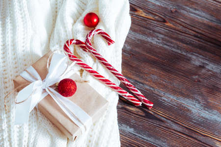 lollipops, red Christmas balls, gift on a white sweater on a wooden